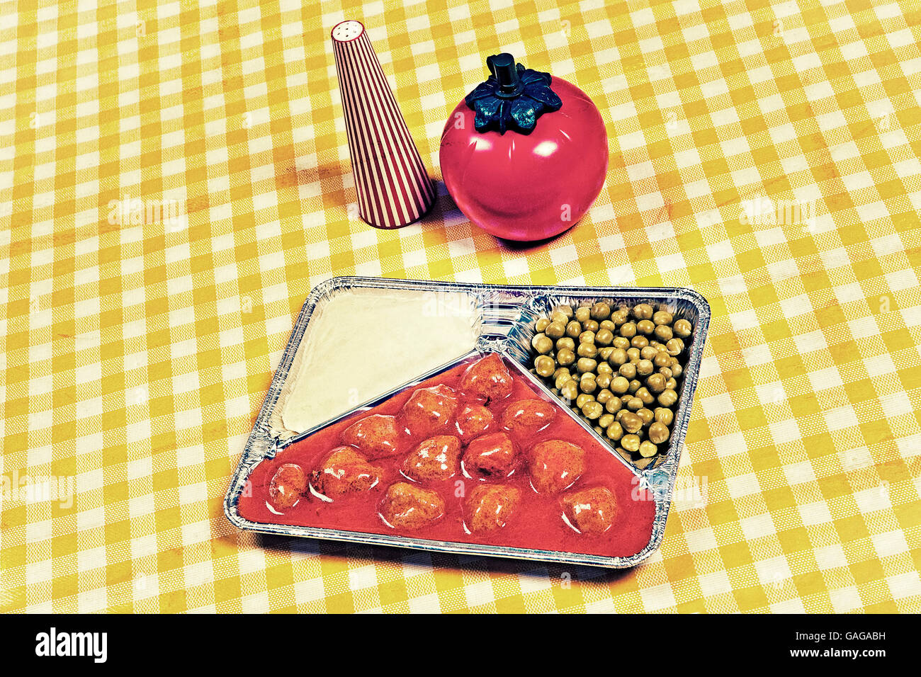 TV dinner tray vintage retro meal aluminum dish on tablecloth with tomato sauce - Stock Image