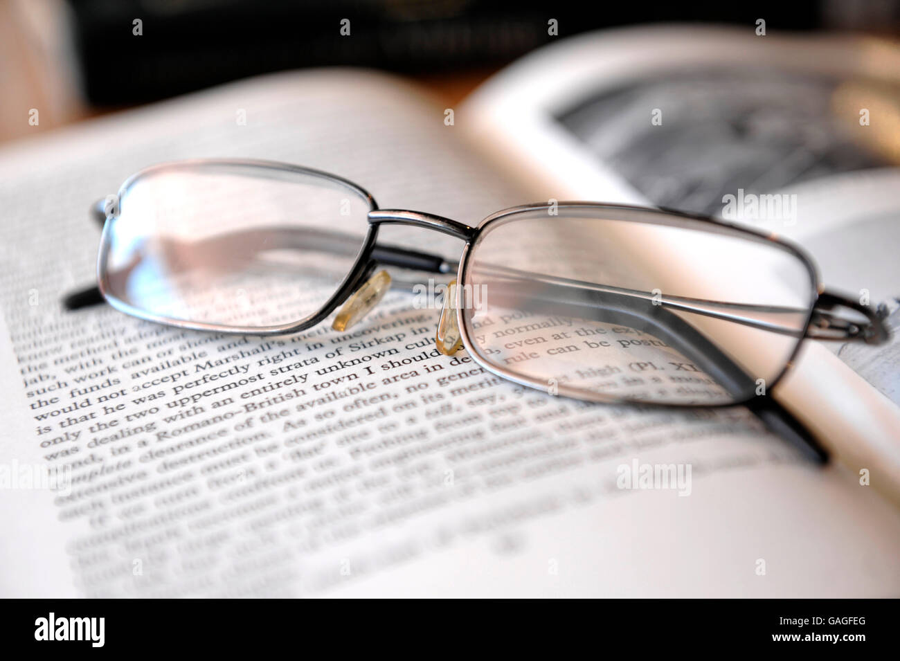 Reading glasses on top of book of antiquity - Stock Image