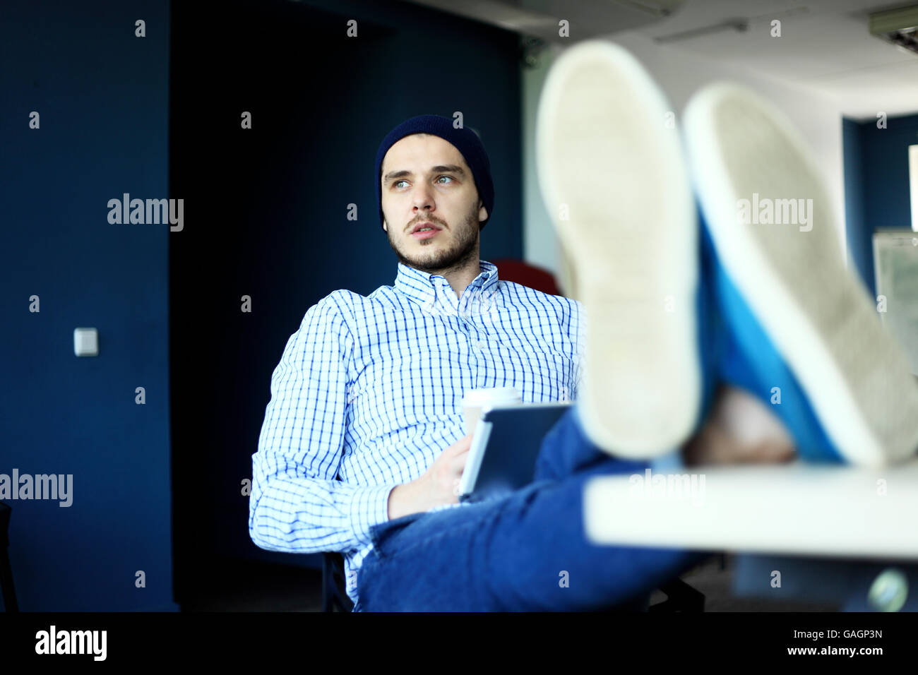 Handsome man working from his home office. Analyze business plans on laptop. Blurred background, film effect - Stock Image