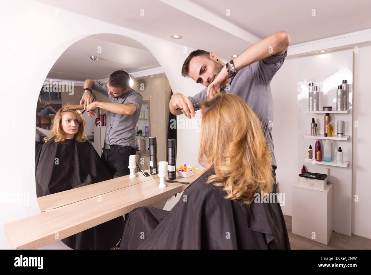 hairstylist cutting hair woman mirror rear view - Stock Image