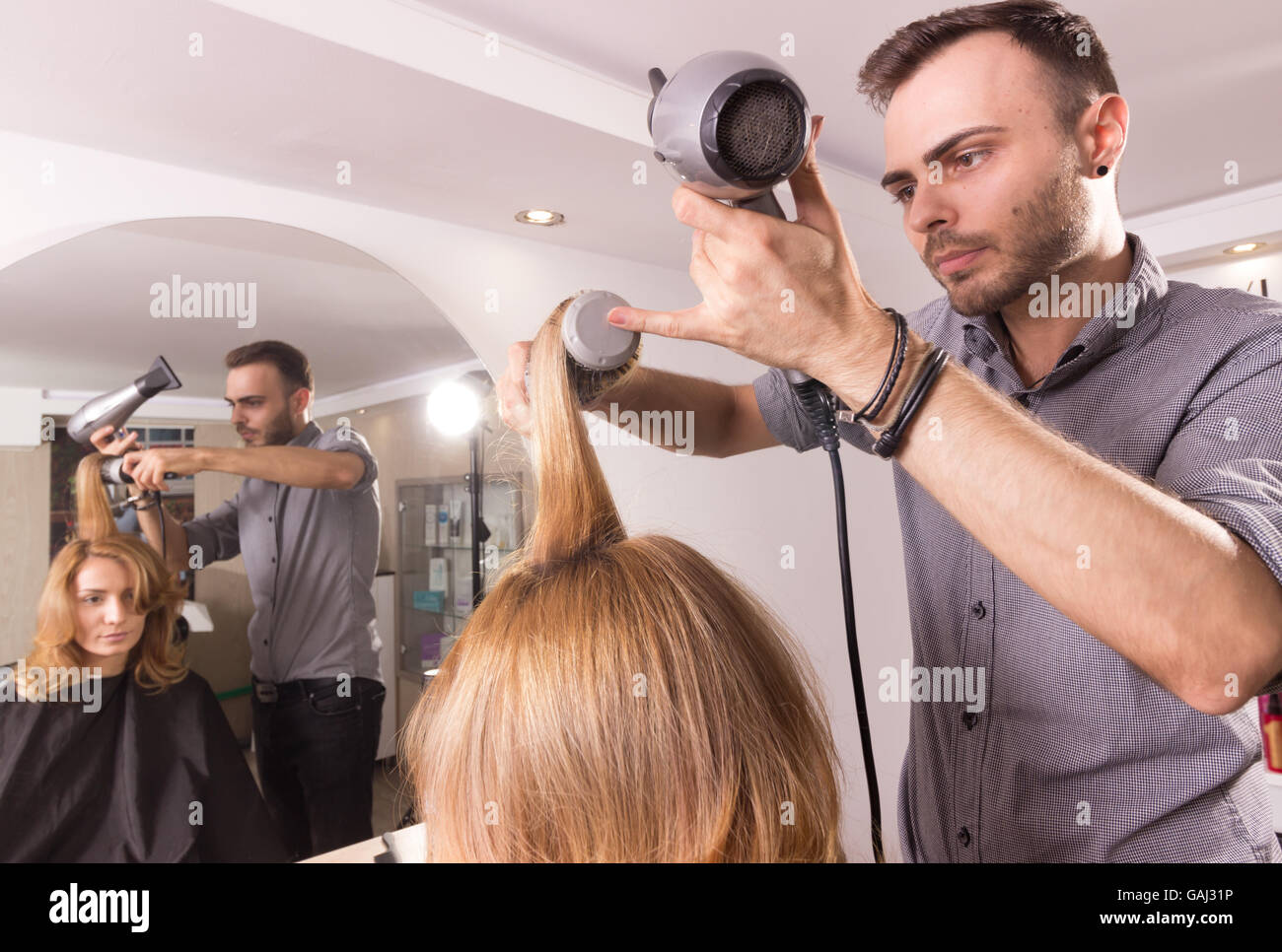 man hairstylist blow drying comb roller woman hair, rear view. - Stock Image