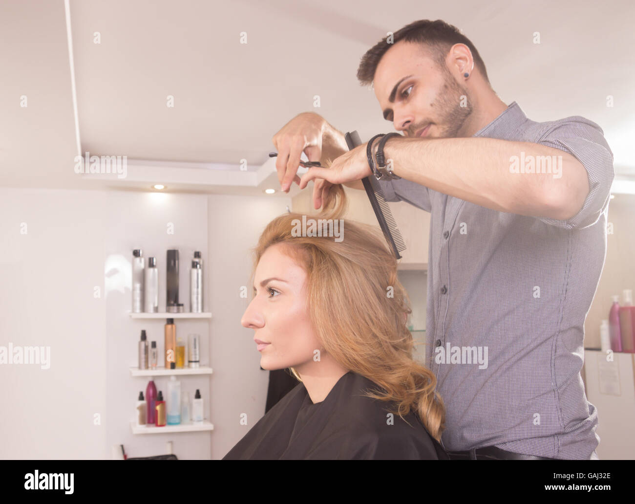 side view, hairdresser cutting woman hair scissors - Stock Image