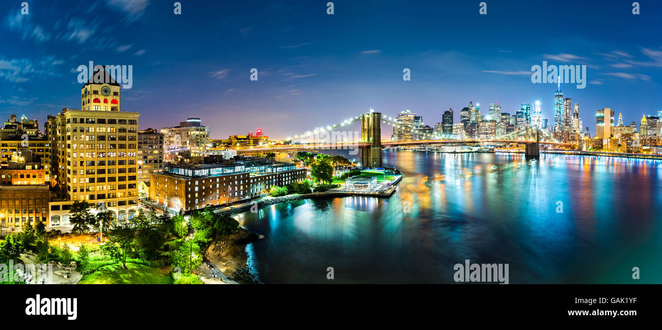 New York City panorama by night. Brooklyn Bridge spans East River linking Manhattan and Brooklyn boroughs - Stock Image