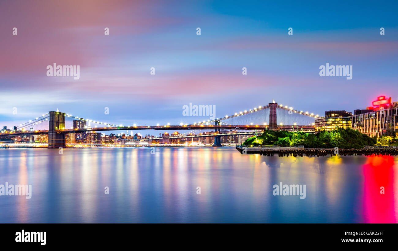 Illuminated Brooklyn Bridge at dusk viewed from Pier2 park in New Yok City - Stock Image