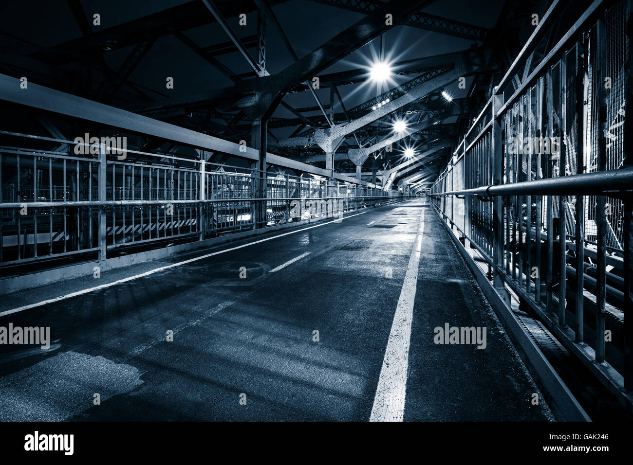 Moody monochrome view of Williamsburg bridge pedestrian walkway by night in New York City - Stock Image