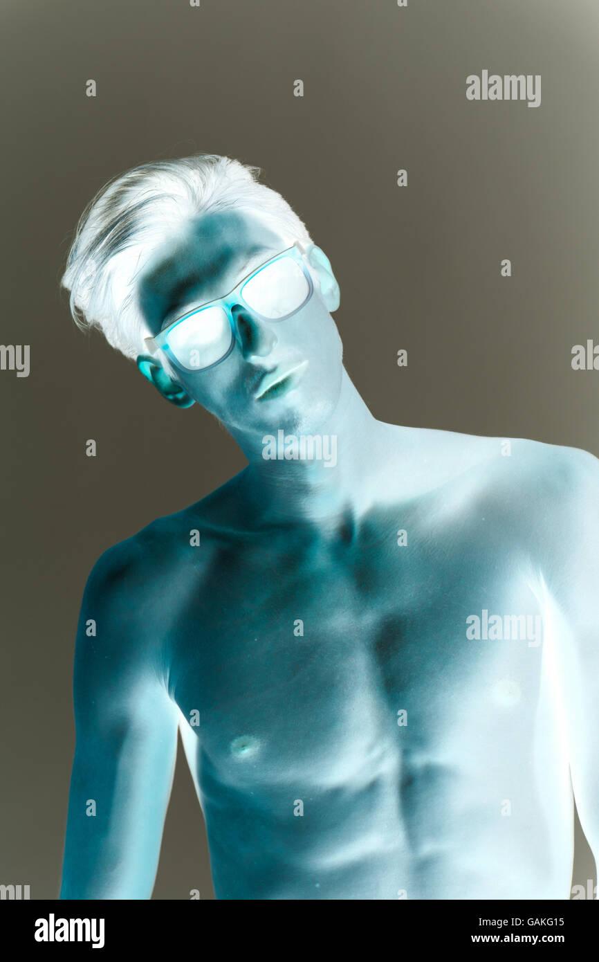 Skinny model showing abs, wearing eyeglasses. Inverted tone negative effect. - Stock Image