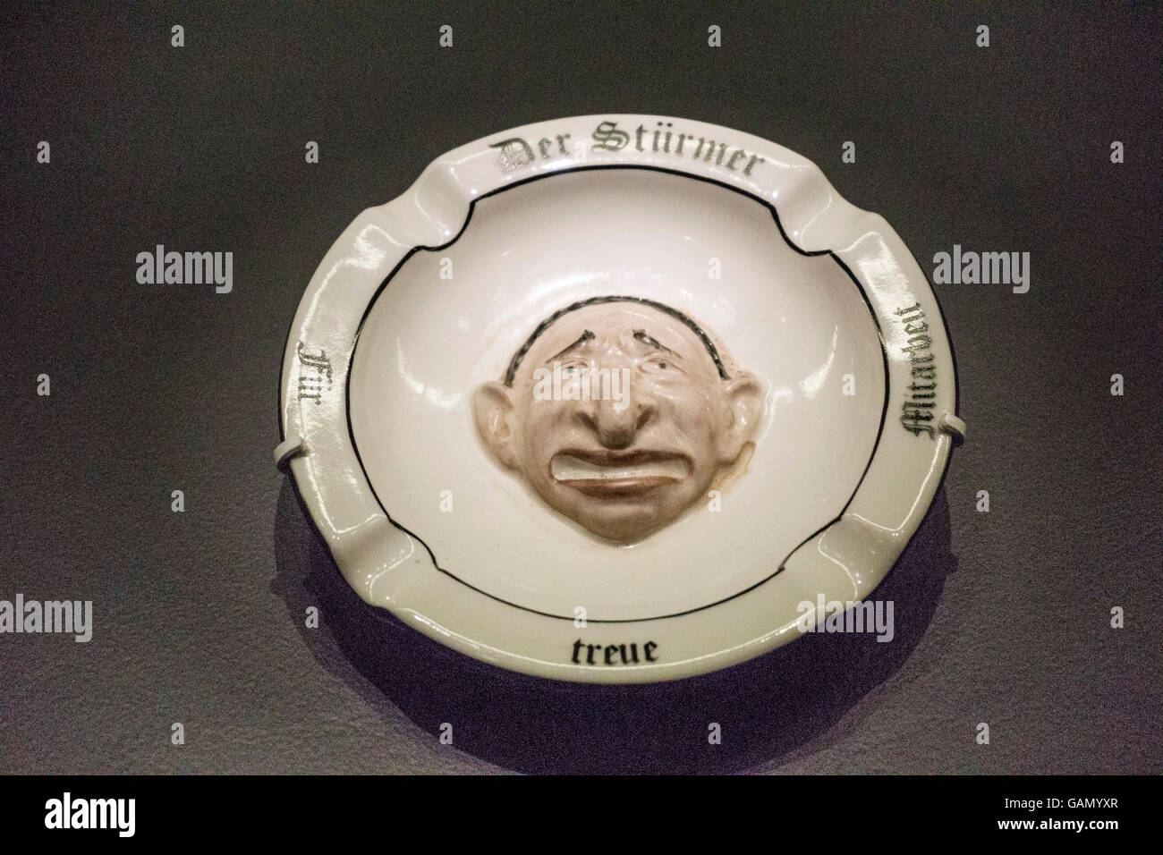 anti Semitic ash tray with worried face of Jewish male caricatured in low relief displayed among artifacts of Nazi - Stock Image