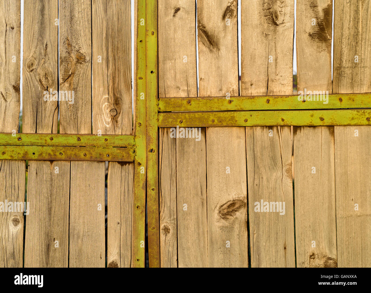 Rustic and aged green painted metal door frame of a village garage ...