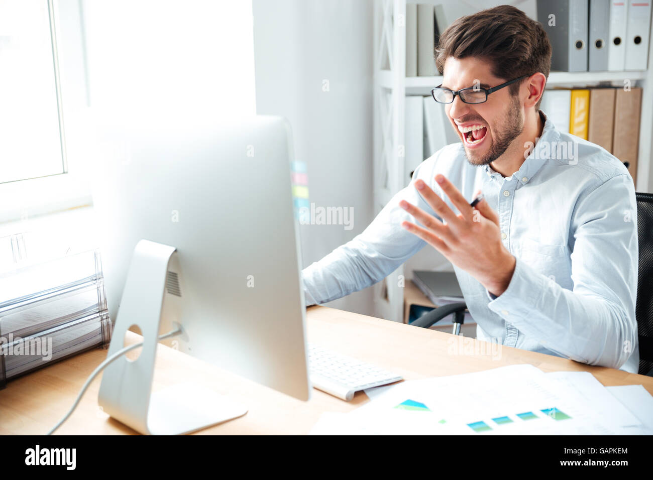 Angry mad young businessman working with computer and shouting in office - Stock Image