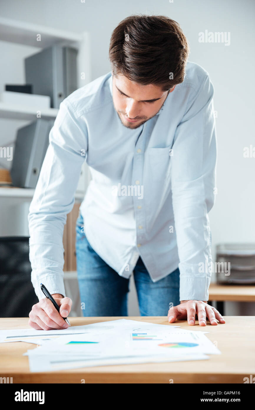 Serious young businessman staning and writing on the table in office - Stock Image