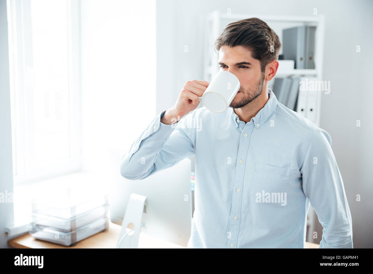 Handsome young man standing and drinking coffee in office - Stock Image