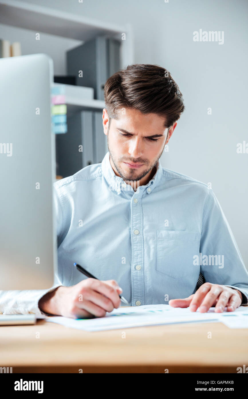 Confident young businessman sitting at the table and signing document in office - Stock Image