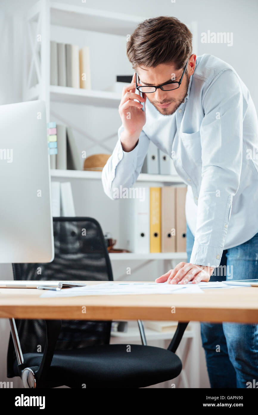Businessman closing a deal signing documents at desk in office wearing white shirt Stock Photo