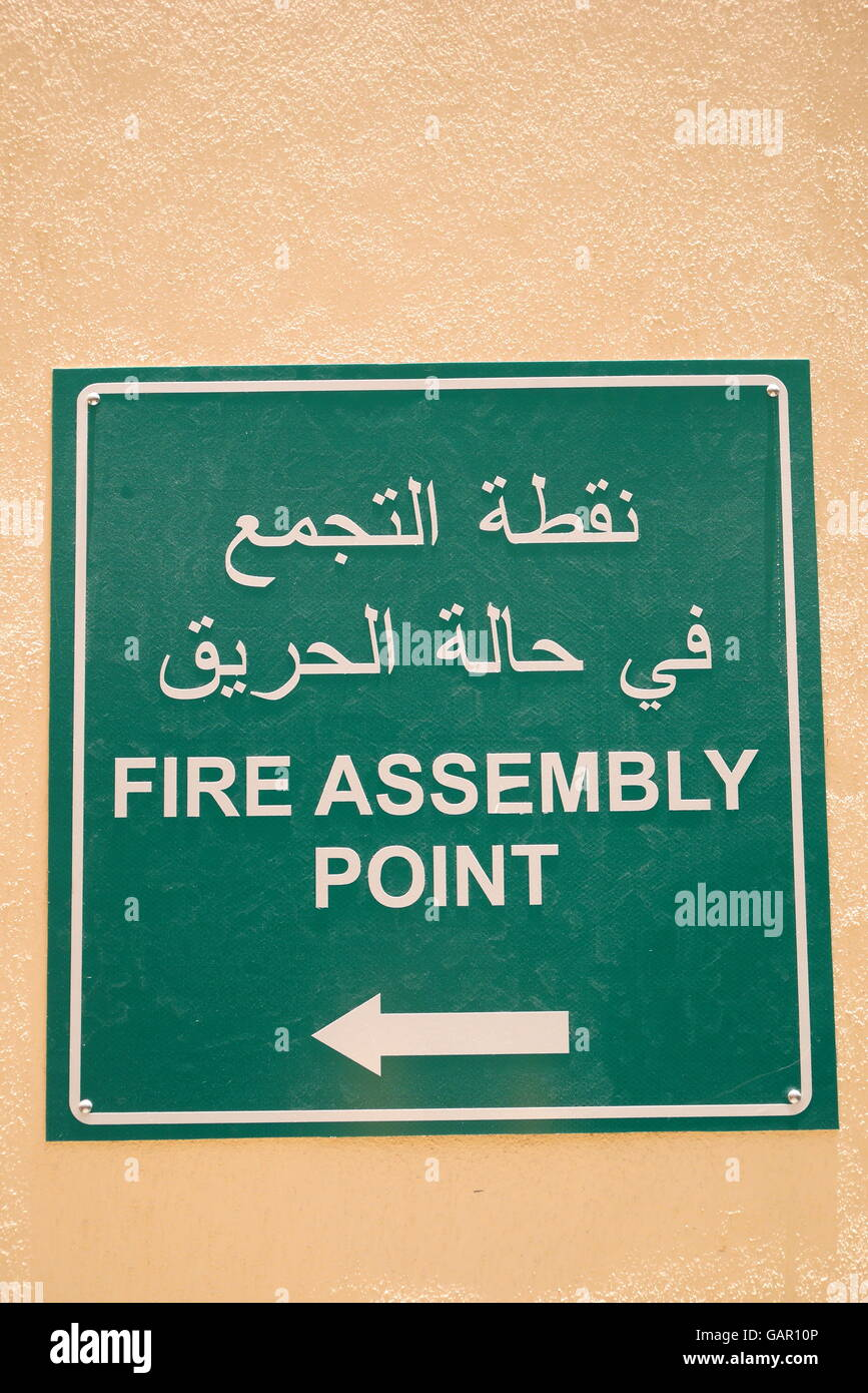 Sign in Arabic and English indicating Fire Assembly Point at a hotel, Kingdom of Bahrain - Stock Image