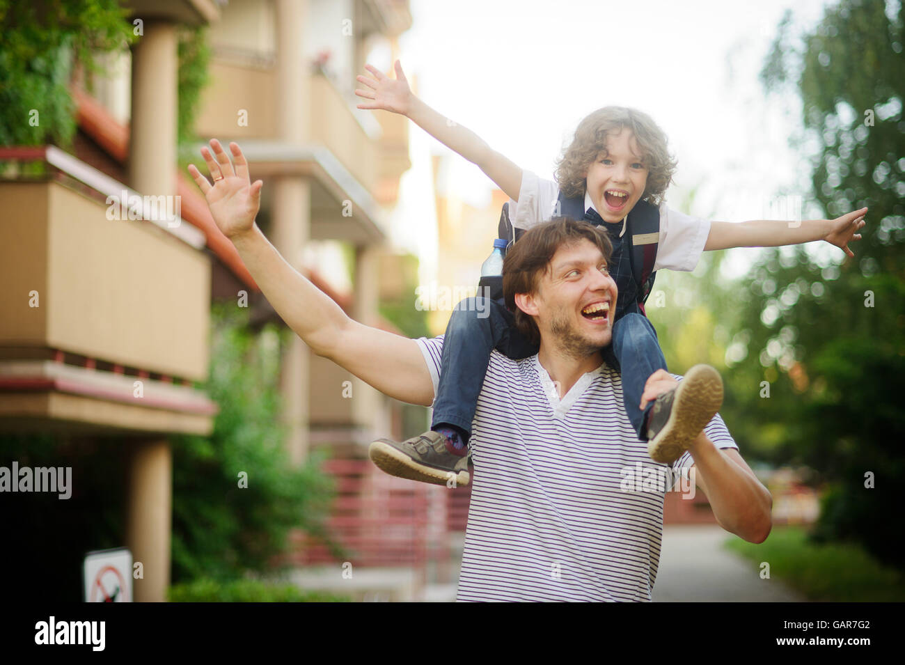 First grader sitting on the shoulders of his father. He is very happy. Father and son pretending to fly. They have - Stock Image