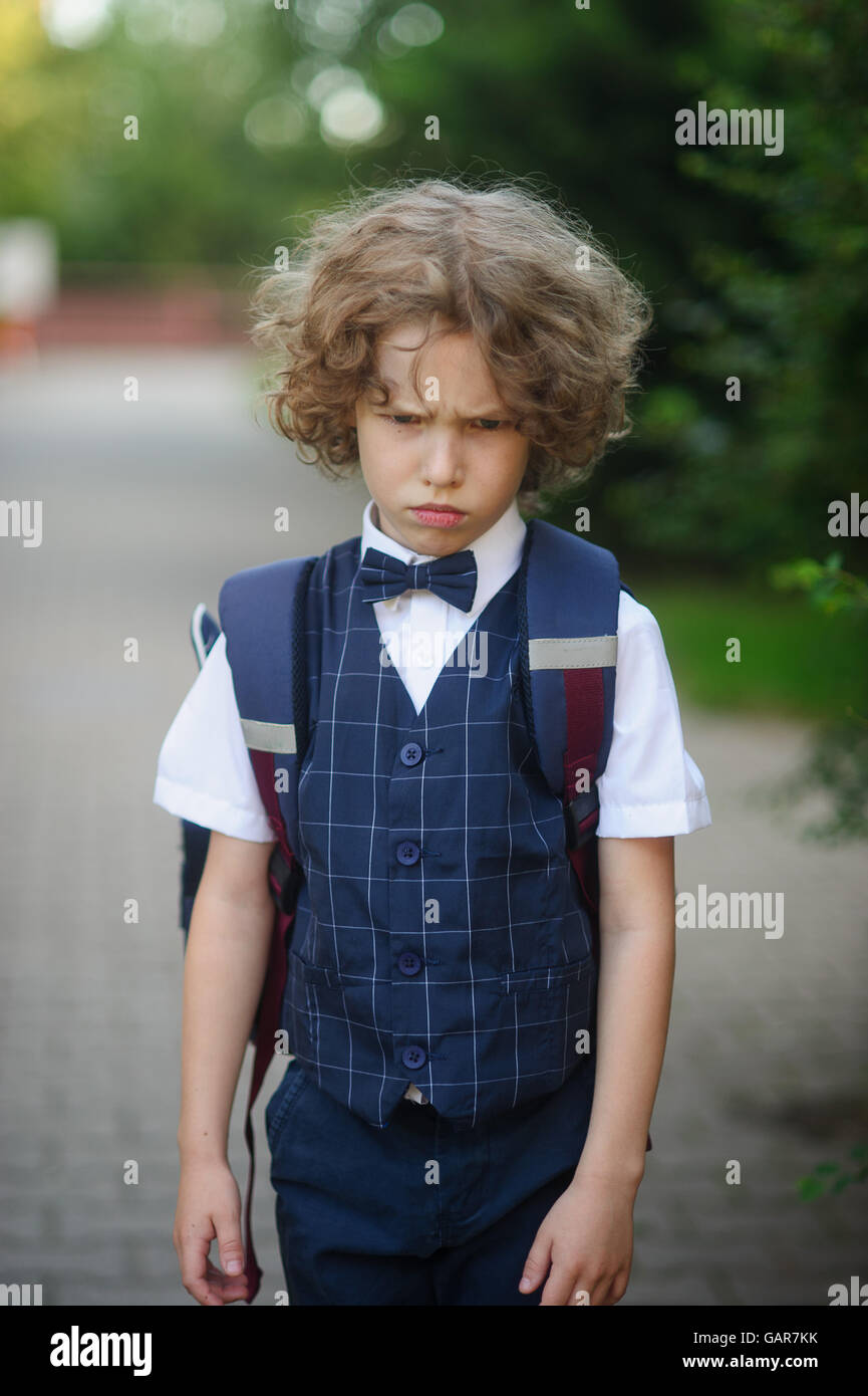 Little schoolboy stands in the school yard with an angry expression on his face. Boy bend one's brows. Curly - Stock Image