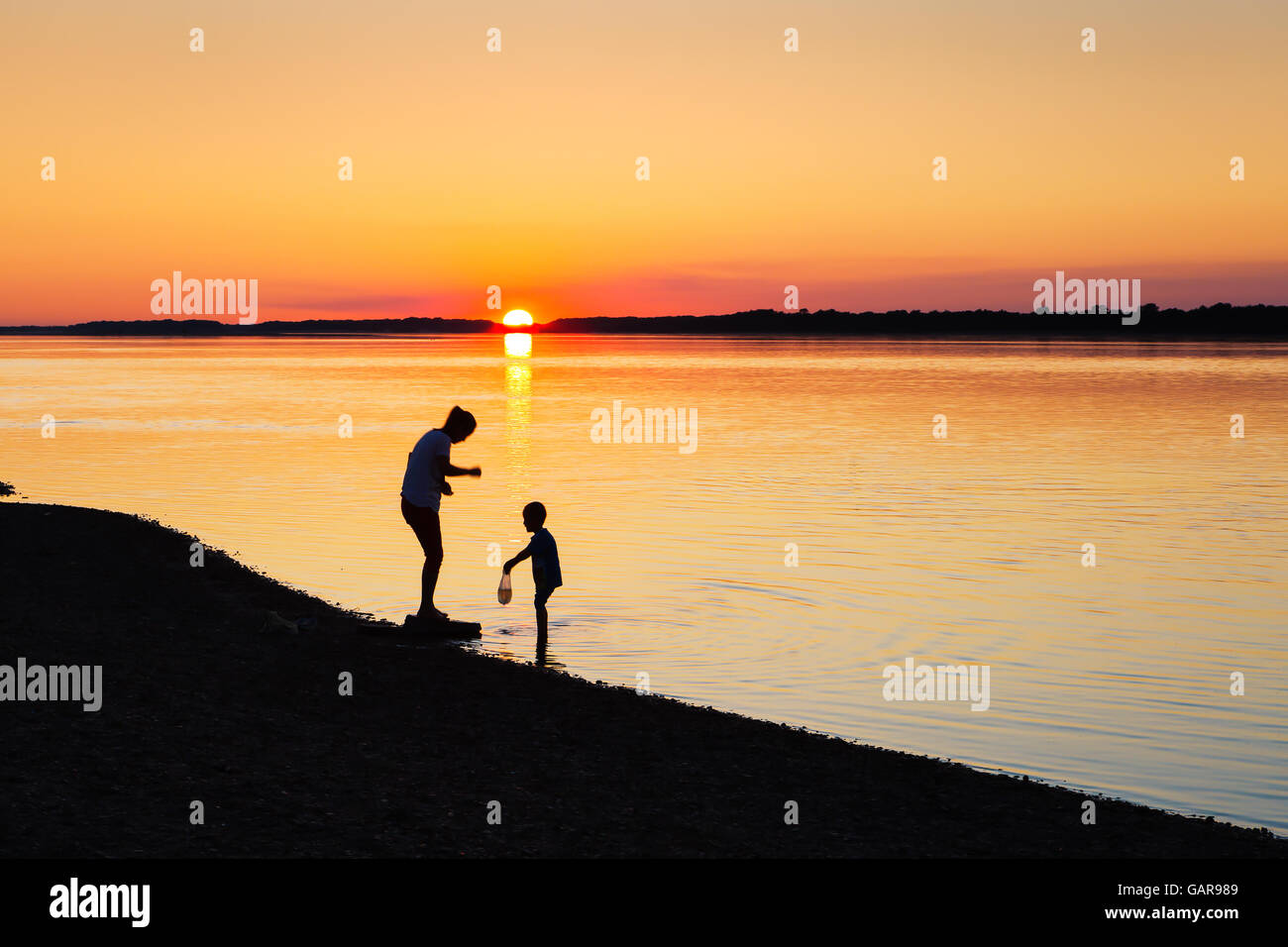 mother and son enjoying their family time alongside river during beautiful sunset - Stock Image