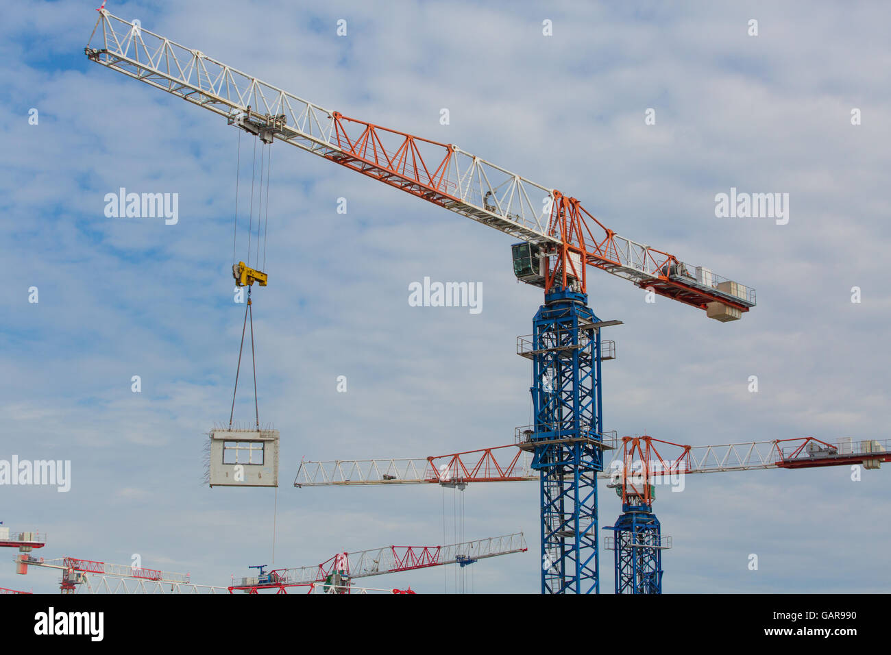 Tower cranes lifting precast fabrication block on the air - Stock Image