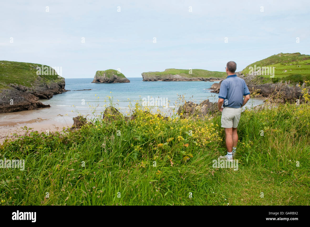 Man looking at Borizu beach from a hill. Barro, Asturias, Spain. - Stock Image