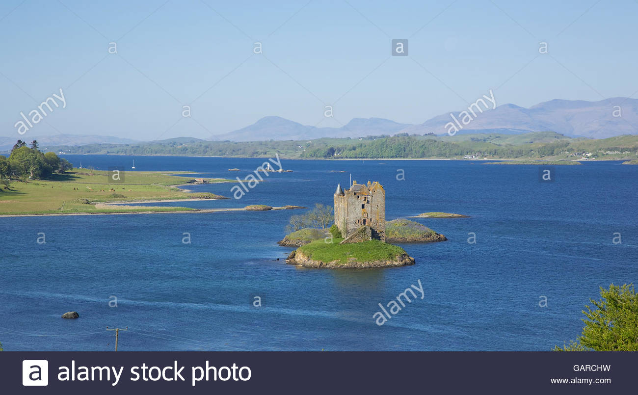 Castle Stalker on an islet on Loch Laich, an inlet off Loch Linnhe, with a view beyond to the hills of Morvern, - Stock Image