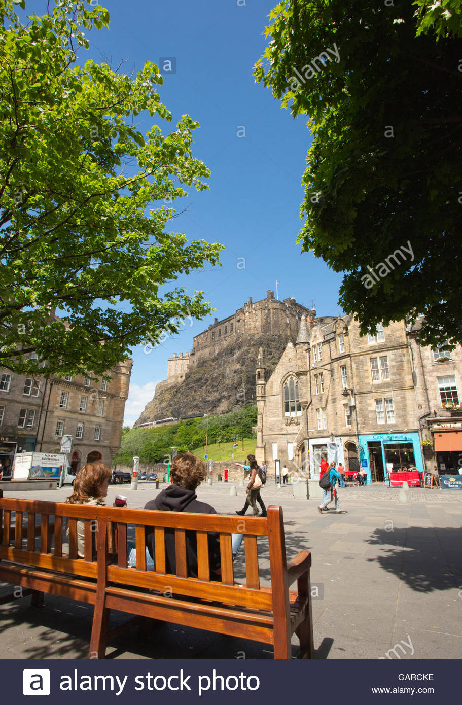 People in the Grassmarket with a view to the castle behind in the city centre of Edinburgh, Scotland. - Stock Image