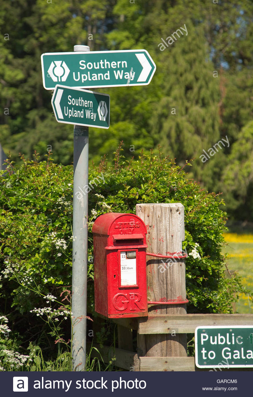 A Royal Mail post box and sign post for the Southern Upland Way - a long distance walking route at Fairnilee or - Stock Image