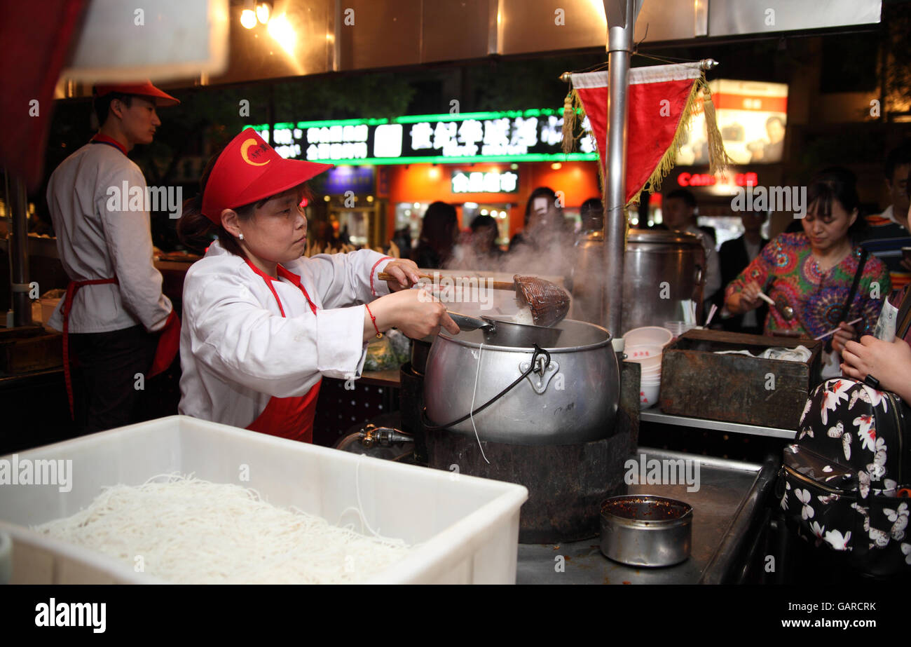 Young Chinese woman serves hot noodles to clients from a pot with boiling water at a fast food stand she works at. - Stock Image