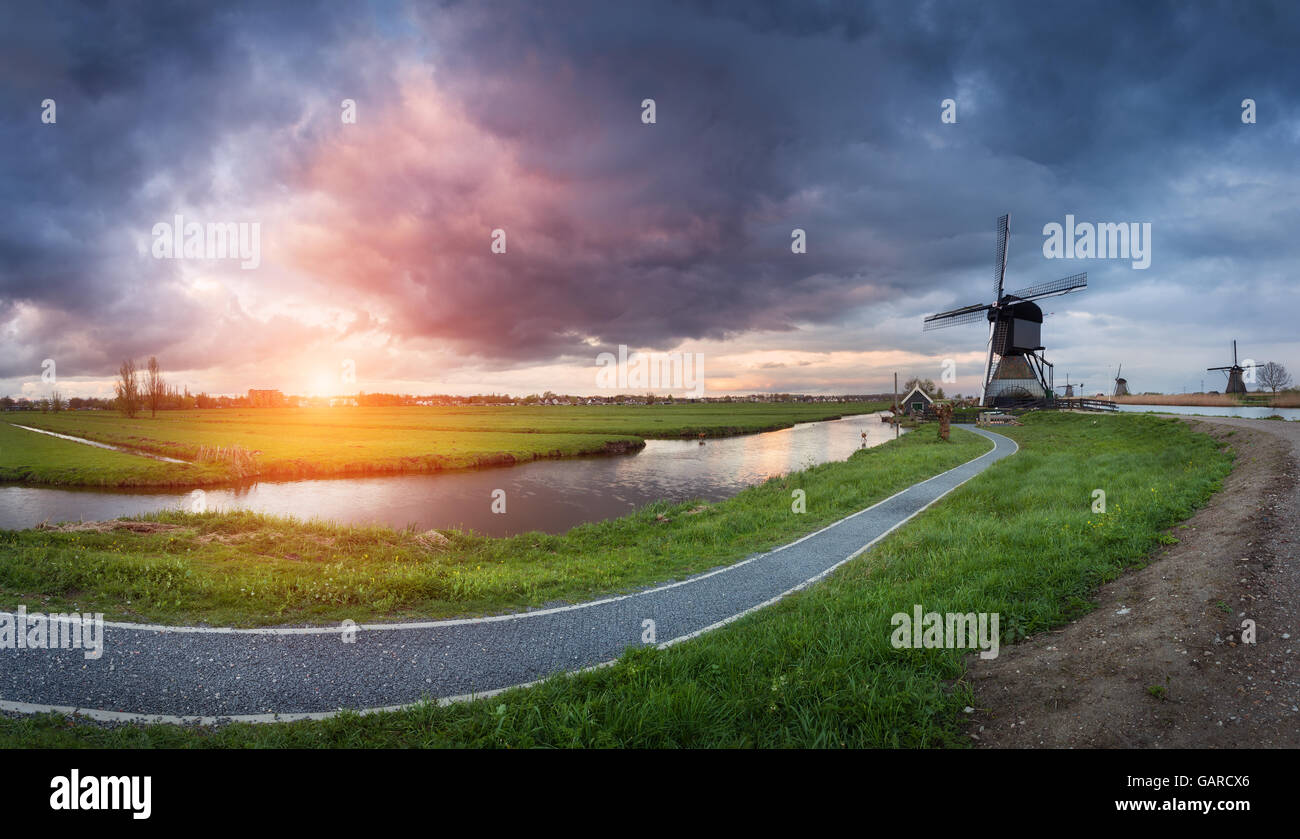 Landscape with traditional dutch windmills and path near the water canals. Clouds at colorful sunset in spring. Stock Photo