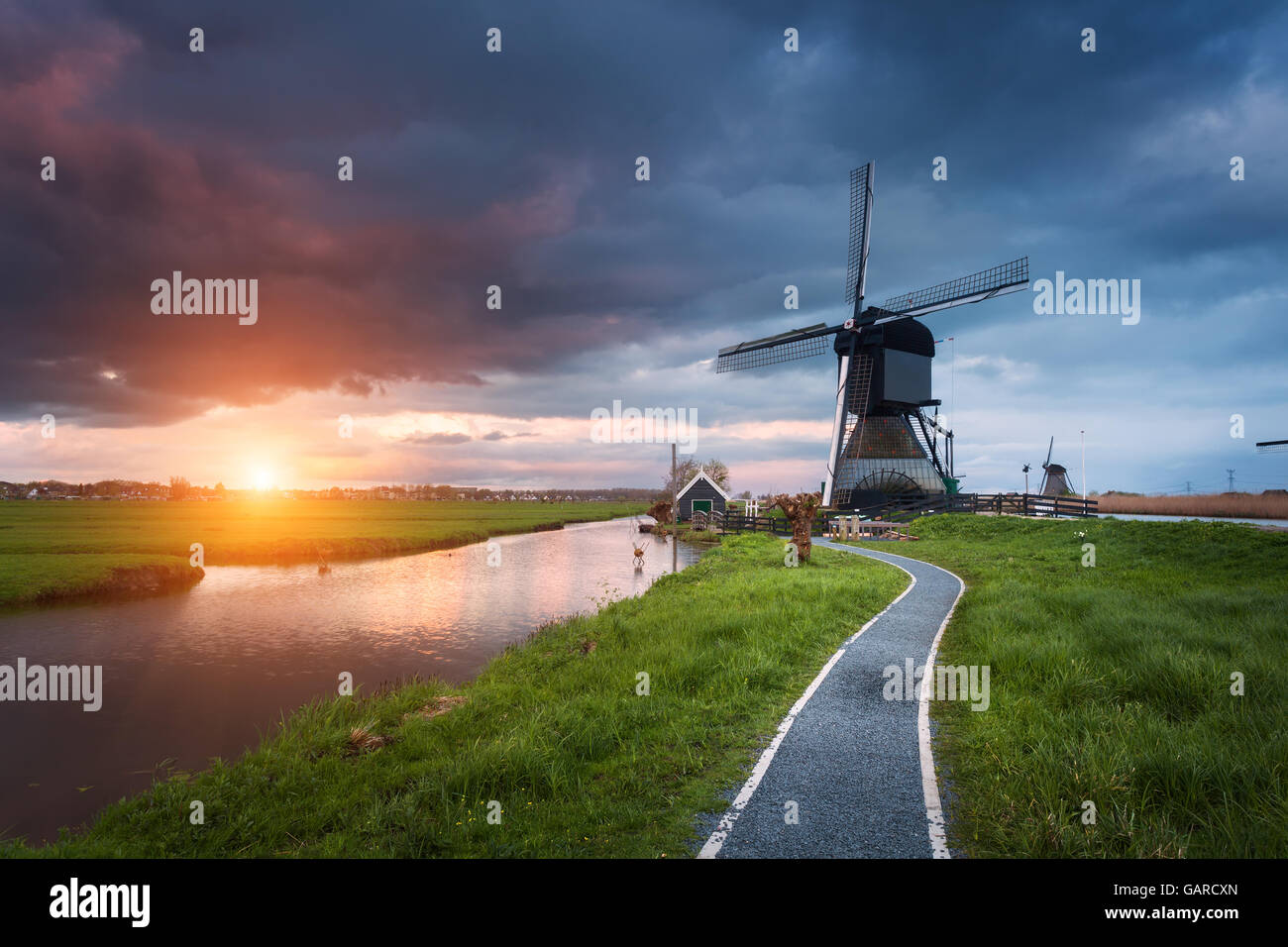Landscape with traditional dutch windmills and path near the water canals. Clouds at colorful sunset in spring. - Stock Image