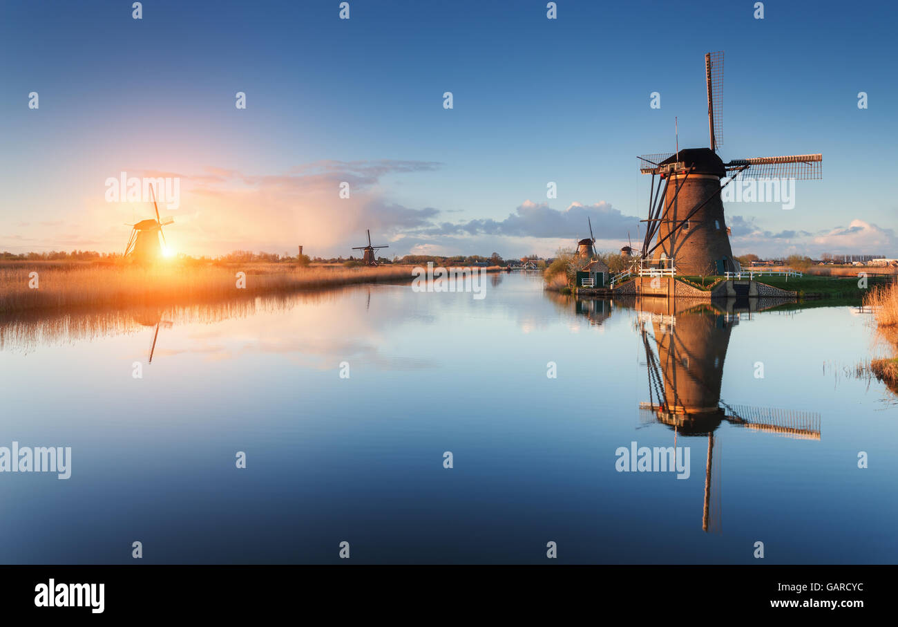 Beautiful traditional dutch windmills near the water channels with reflection in water at colorful sunrise in famous - Stock Image