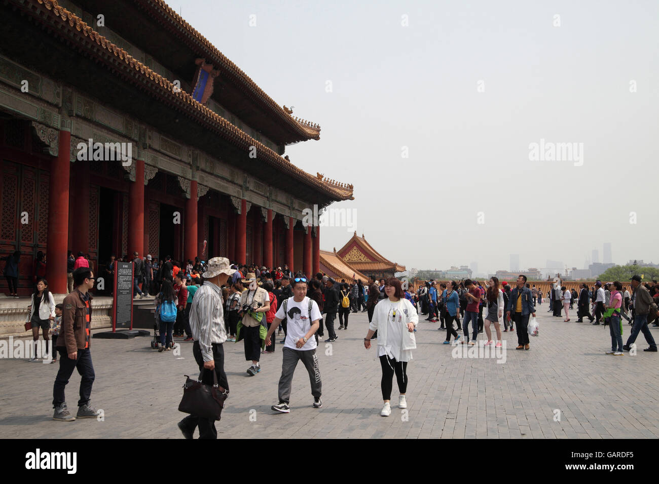Chinese people and foreigners, tourists walk by the Hall of Preserving Harmony in the Forbidden City. Beijing, China. - Stock Image