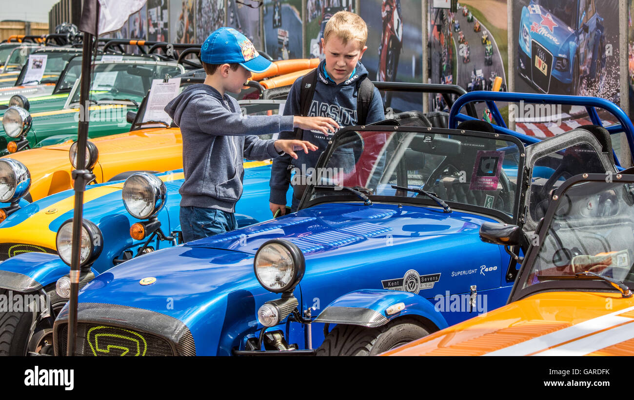 Two young boys looking at a row of Caterham 7s at Brands Hatch - Stock Image