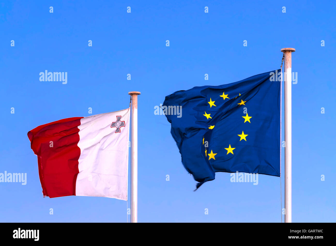 Maltese and EU flags next to each other on the blue sky waving in the wind - Valletta, Malta - Stock Image