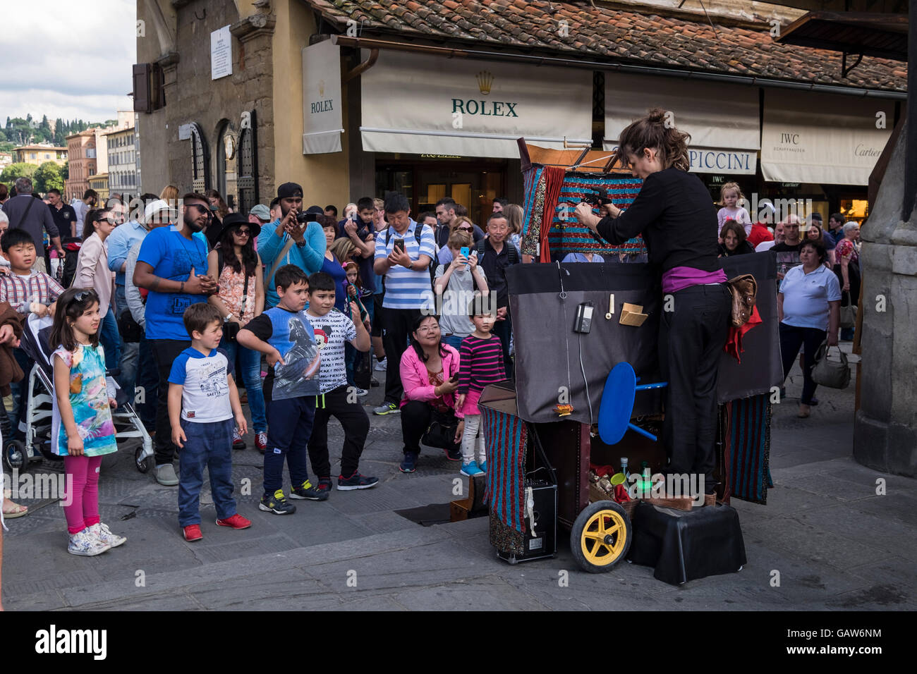 Crowds of tourists and kids watching a puppeteer on the Ponte Vecchio bridge in Florence, Tuscany, italy - Stock Image