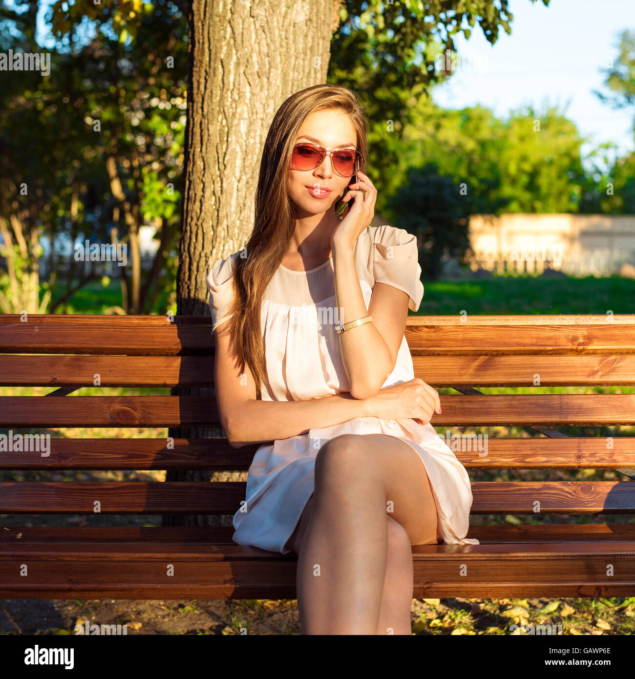 3c10a0819d1 Beautiful emotional brunette girl laughing on the phone in the park summer  glasses pink dress