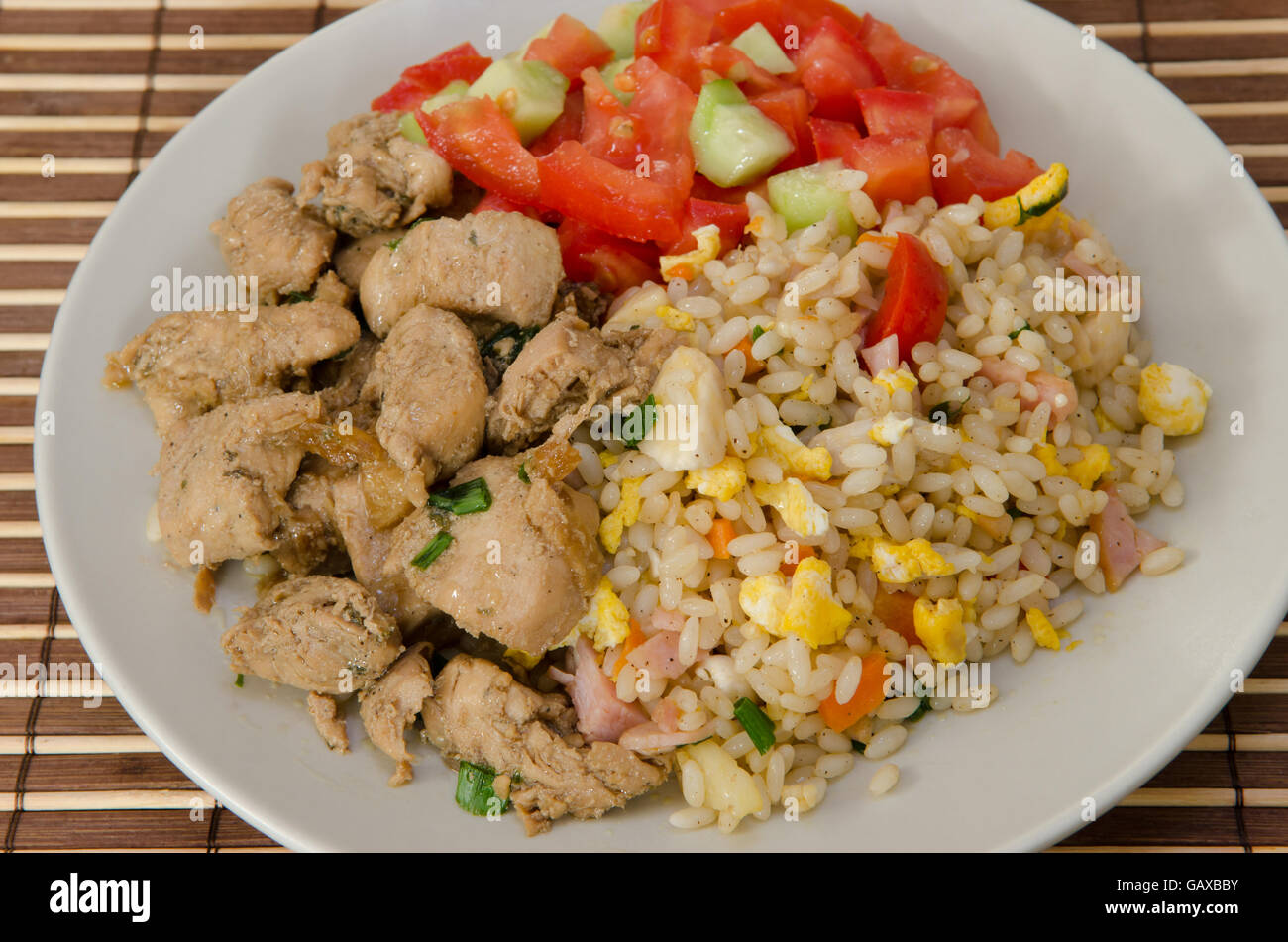 pork with egg fried rice and mixed salad on a plate Stock Photo