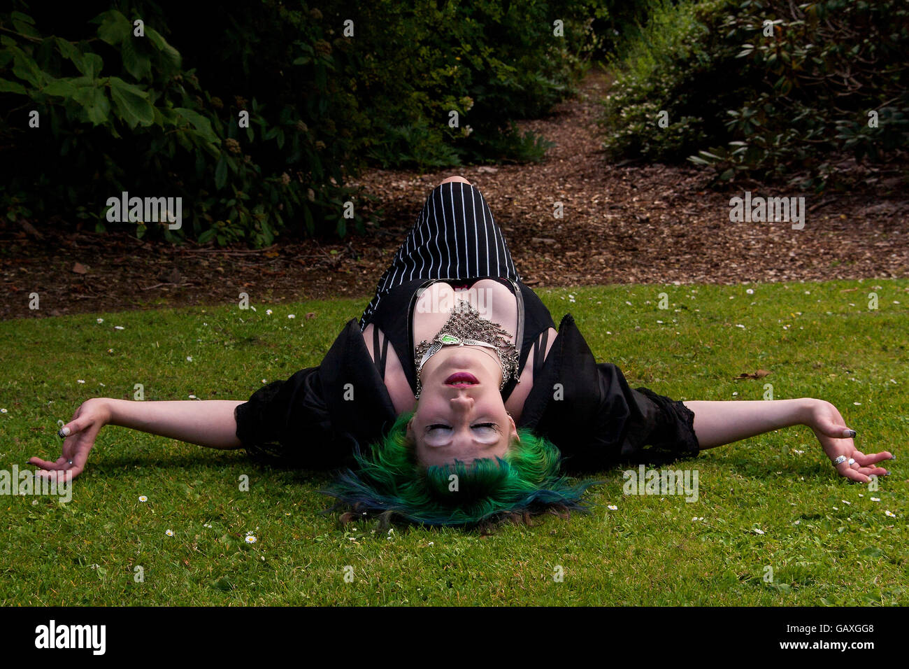 A woman wearing an Alice In Wonderland style outfit lying on the grass sleeping inside the Botanical Gardens in Stock Photo