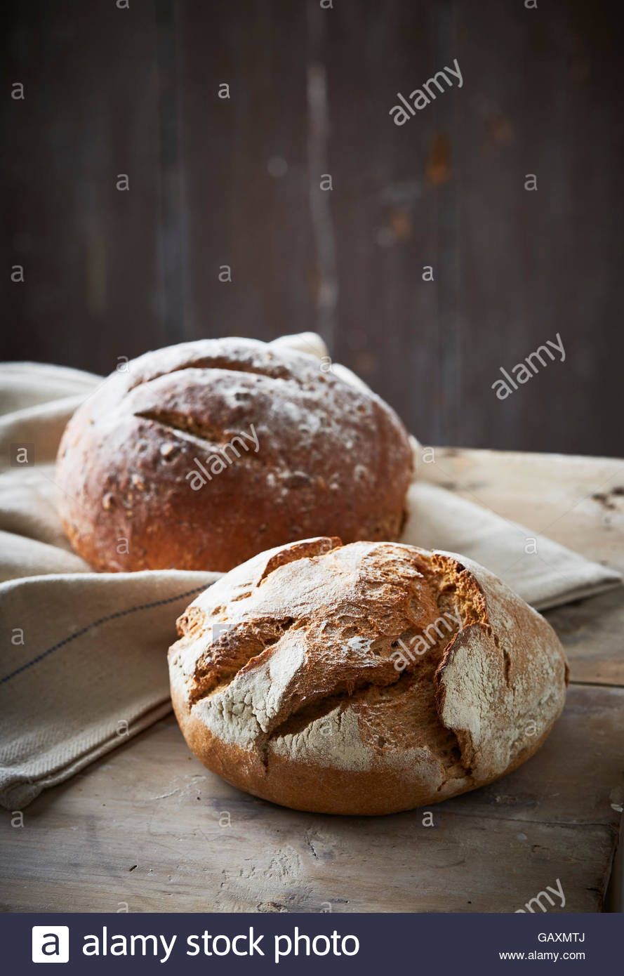 two artisan baked loaves on dark background with linen cloth - Stock Image