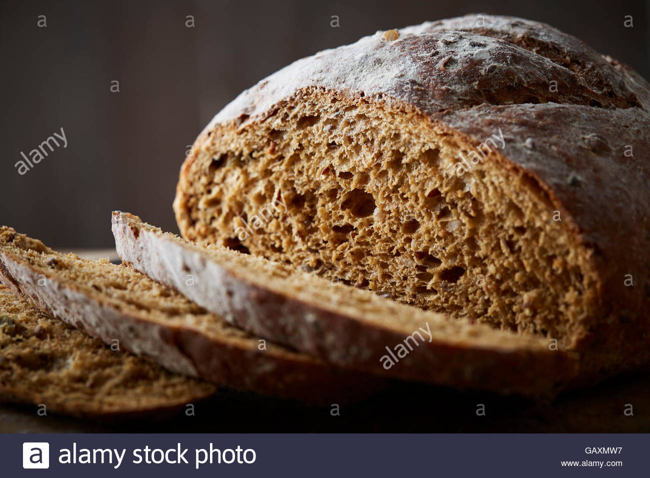 artisan brown loaf of bread on dark background - Stock Image