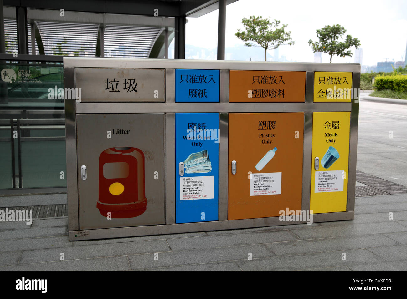 A nicely designed garbage can with different disposal spaces for general litter, waste paper, plastics and metal. - Stock Image
