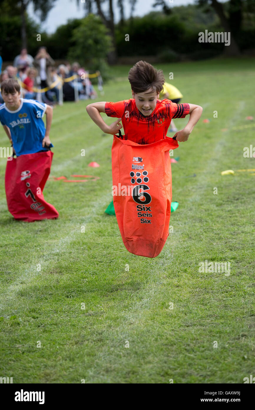 Child competing in sack race St James Primary School sports day Chipping Campden UK - Stock Image