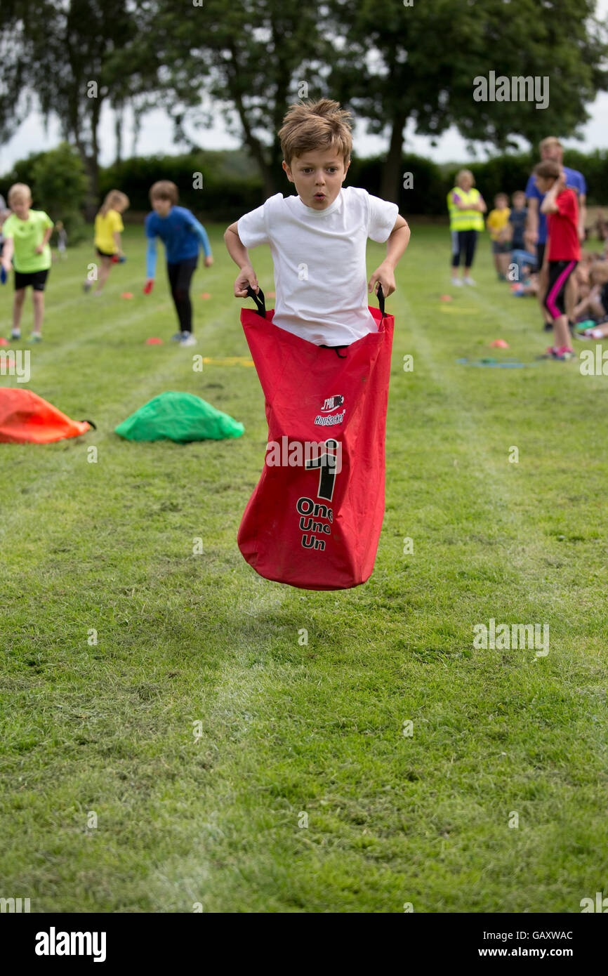 Boy competing in sack race St James Primary School sports day Chipping Campden UK - Stock Image