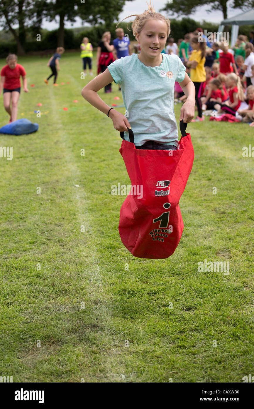 Girl competing in sack race school sports day St James Primary Chipping Campden UK - Stock Image