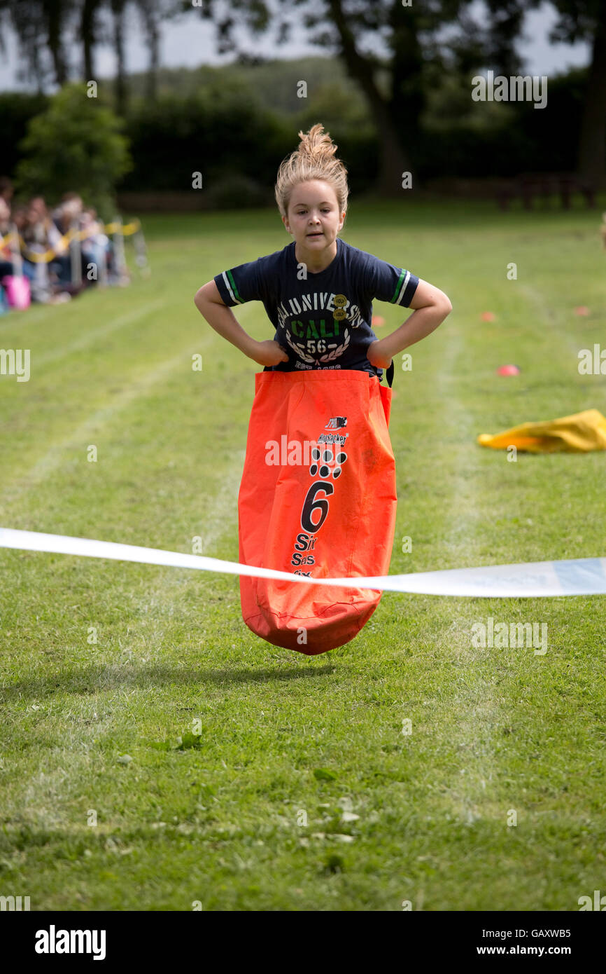 Girl in mid air competing in sack race St James Primary School sports day Chipping Campden UK - Stock Image