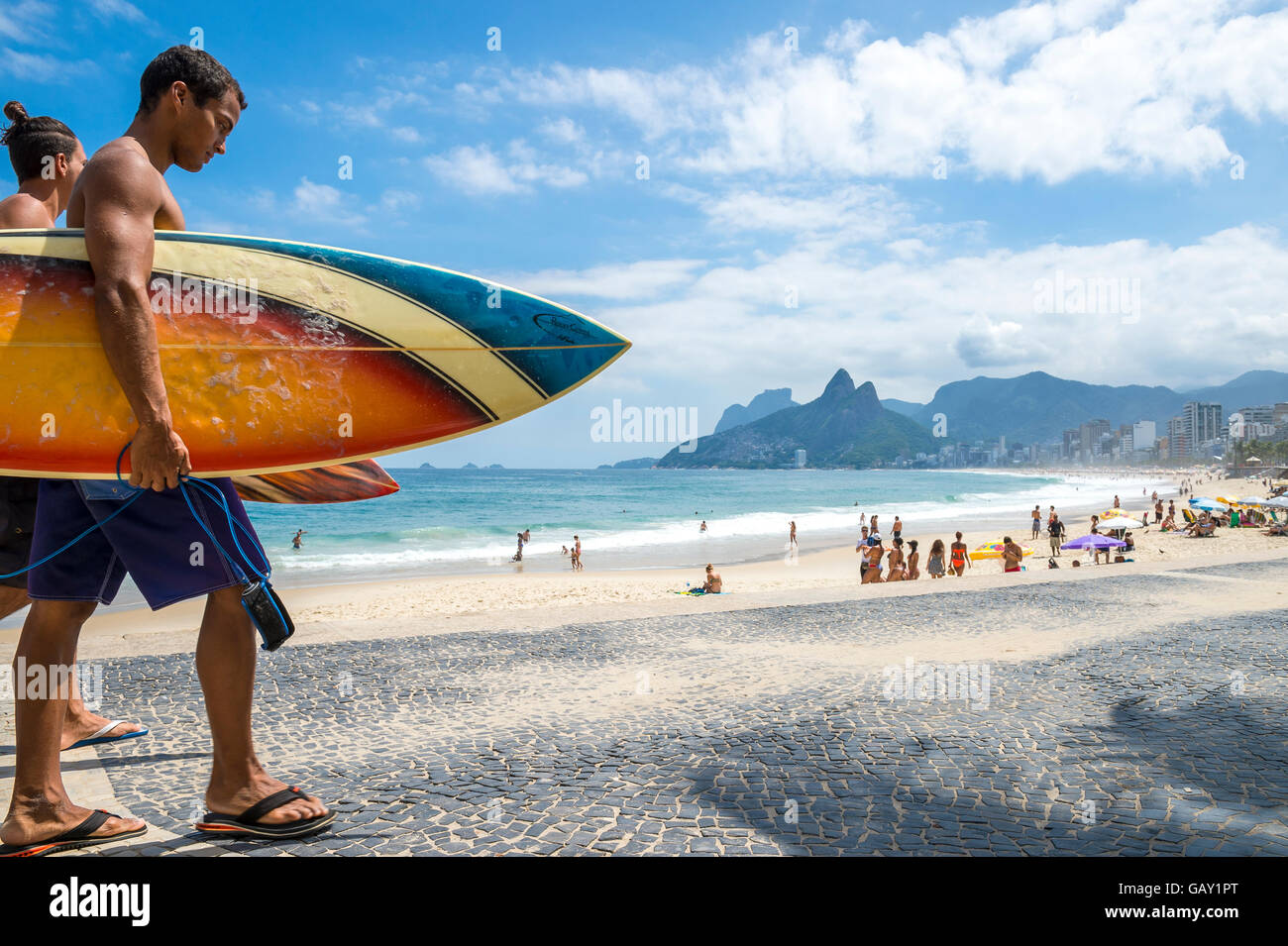 RIO DE JANEIRO - APRIL 3, 2016: Young carioca Brazilian couple walks with surfboards Arpoador, the popular surf - Stock Image