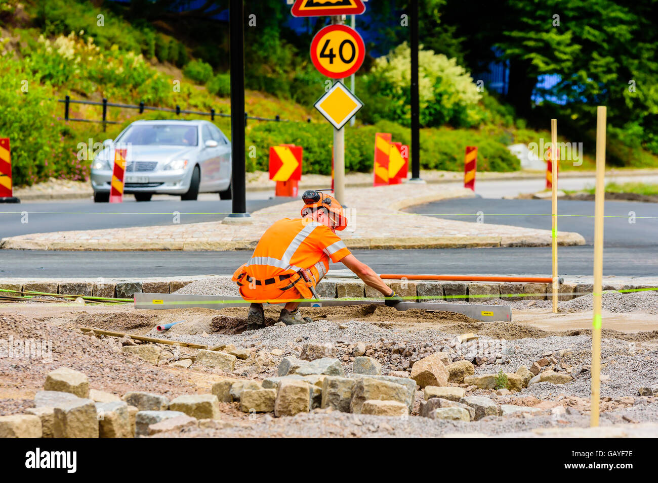 Motala, Sweden - June 21, 2016: Male worker squatting down and leveling the gravel building a roundabout. Car and - Stock Image