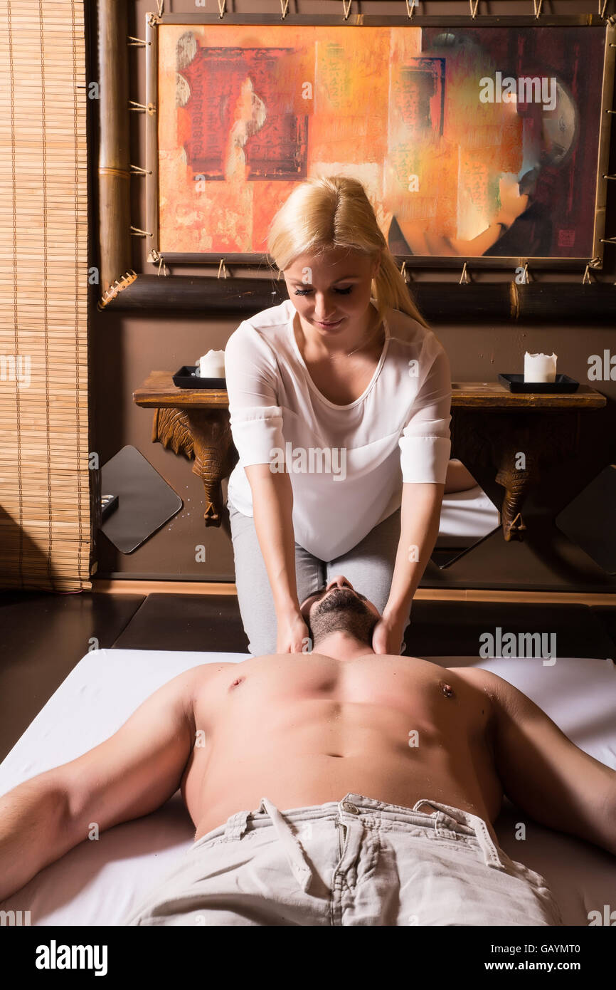 A young masseuse applying a head massage to a young male. Stock Photo