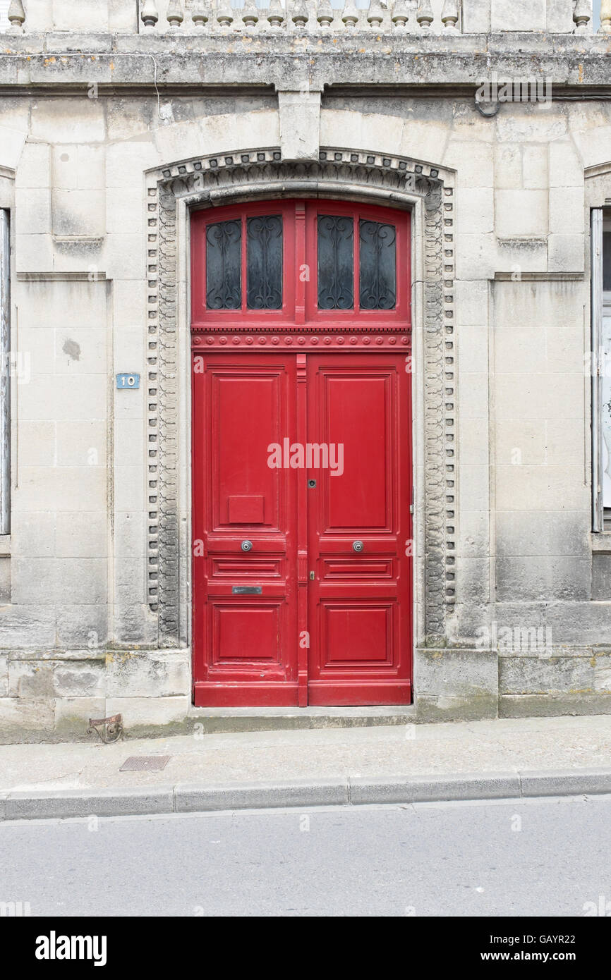 Red Wooden Double Doors At The Entrance To An Old Stone Building In