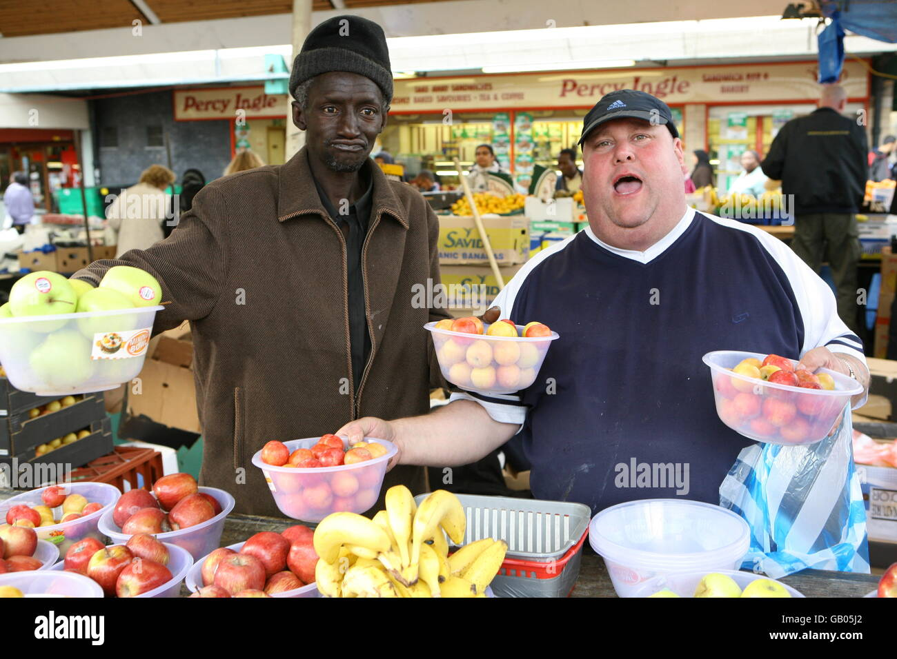 Neil Stockwell, second generation stallholder in Queens Market, Newham, East London and assistant Alagi Nyang posing - Stock Image