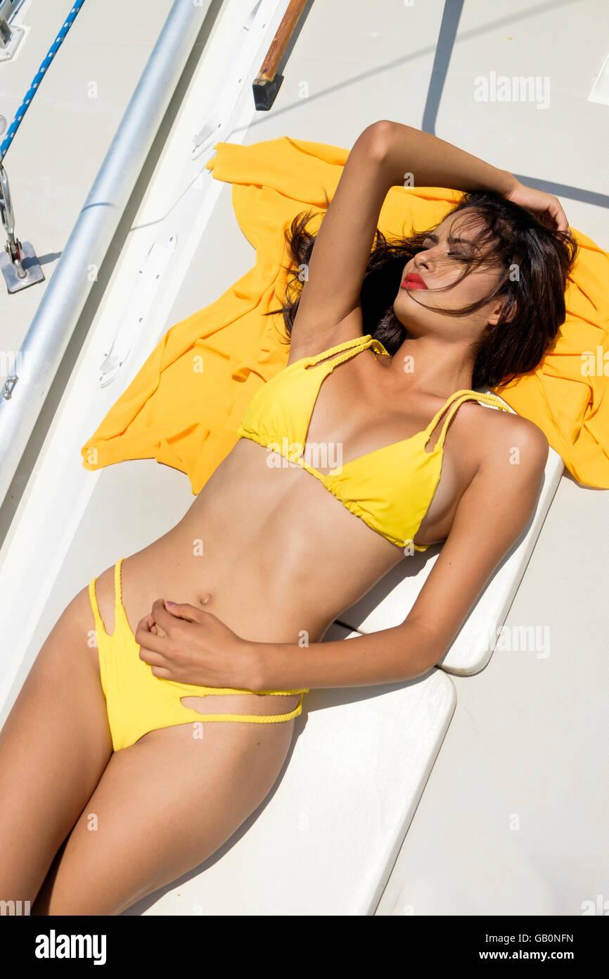 Attractive hispanic woman in yellow bikini tanning on board of a sail boat. Sailboat tour, Riviera Nayarit, Mexico - Stock Image
